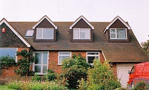 A series of pitched mini-dormers on a gable-ended property.