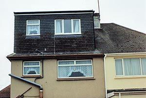 Flat roof dormer on a hip roofed property.
